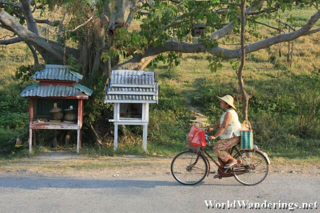 Bicycle Passes by a Water Station by a Nat Shrine