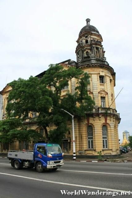 Truck Passes By a Colonial Building in Yangon